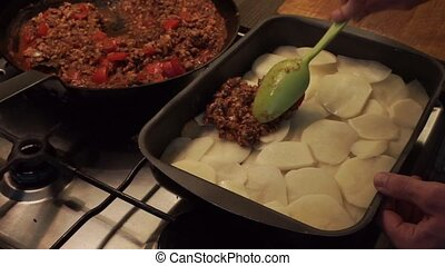 Putting meat sauce on sliced potatoes - Putting meat sauce...
