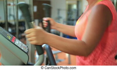 Woman trains on stepper machine in gym. Concept of health...