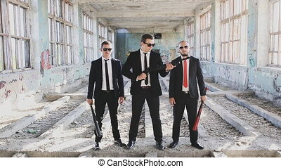 three criminals with weapons in an abandoned building -...