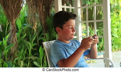 Child relaxing with smartphone - Young boy playing with...