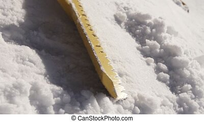 Men clear snow from slope by shovel at ski resort. Sunny day. Working. Snowdrift