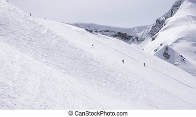 Ski resort. Snowboarders ride on slope. Skiers. White mountain. Sunny day. Speed