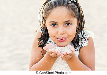 Face shot of girl blowing sand.