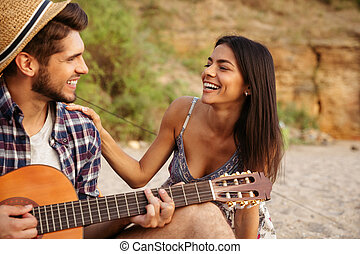 Man playing guitar for his girlfriend sitting at the tent