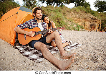 Young happy couple sitting at the tent and playing guitar