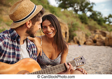 Young happy couple playing guitar while sitting at the beach