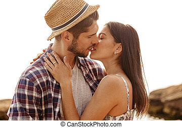 Beautiful young couple standing and kissing on the beach -...