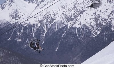 Landscape of snowy mountains in sunny day. Ski resort. People ride on ski lifts.