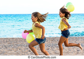 Two little sisters running together on beach. - Close up...