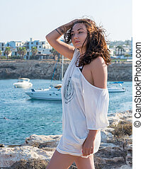Beautiful woman in a white clothes in front of the sea -...