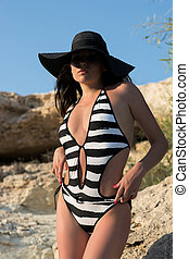 Beautiful young woman in a black hat and in a swimsuit in...