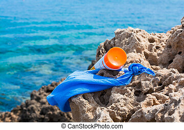 Sunscreen and female blue scarf in front of the sea in the...