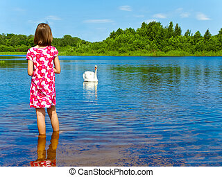 human and nature - girl and white swan at blue lake