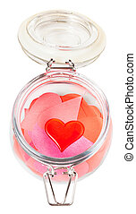 glass heart on pile of paper hearts in open jar - above view...