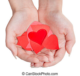 heart above pile of paper hearts on female palms - one red...