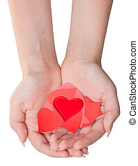 glass heart above pile of hearts on female palms - glass...