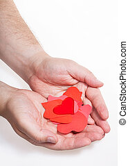 glass heart above paper hearts on male palms - glass heart...