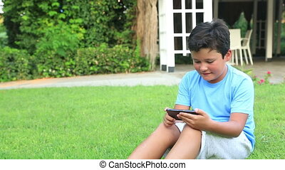 Young boy play smartphone on the grass - Young boy playing...