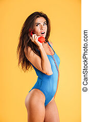 Amazed curly woman in blue swimsuit talking on red telephone...