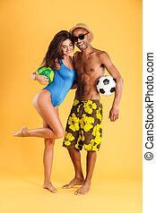 Young happy couple in swimsuits holding balls isolated on...
