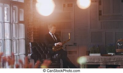 Saxophonist in chair on stage. Jazz vocalist perform at microphone. Lights