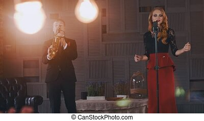 Jazz duet perform on stage. Saxophonist in suit. Vocalist in...
