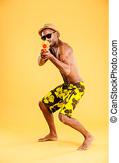 African man in swimwear shooting with water gun - Full...