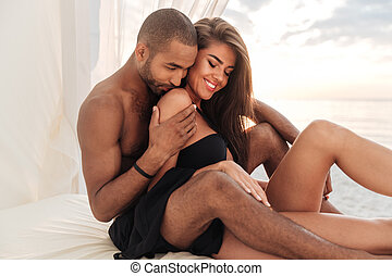 Couple sitting in bed on the beach together - Happy young...