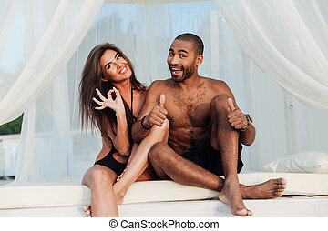 Multircial smiling couple having fun on the beach bed -...