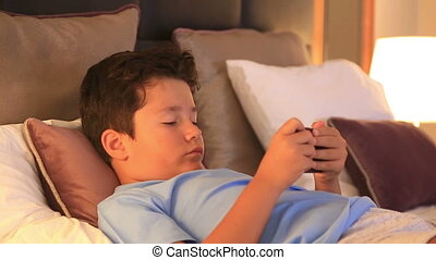 Child with smart phone in bedroom - Child using mobil phone...