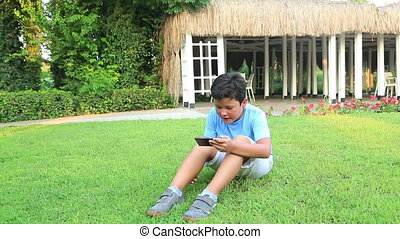 Young boy play smartphone - Child lying on the grass in...