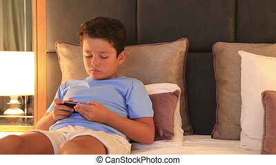 Young burunette child with smart phone in bedroom - Child...