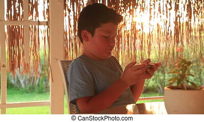 Young boy with smartphone in summer cafee