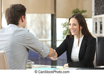 Businesswoman handshaking with client closing deal - Happy...