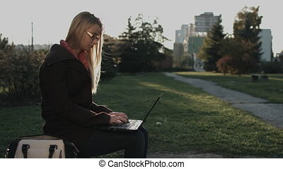 Caucasian lady working on laptop in city park