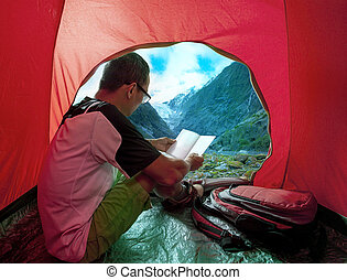 camping man reading a traveling guild book in camp tent...