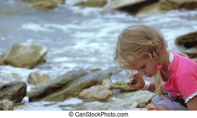 Child throwing stone into sea - Slow motion video of...