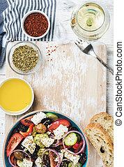 Greek salad with olive oil, bread, herbs and white wine -...