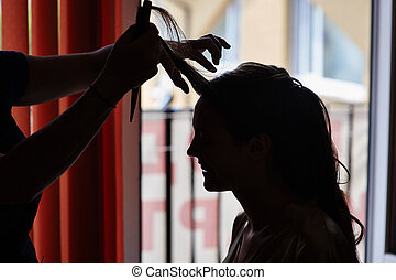 silhouette of Stylist makes make-up bride on the wedding day
