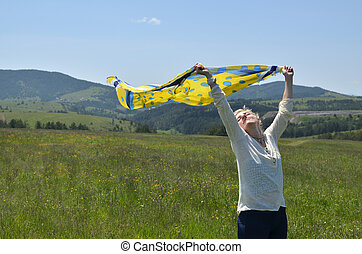 Woman Holding Scarf in Wind - Woman holding yellow and blue...