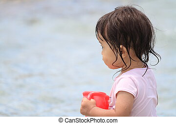 Japanese girl playing with water with watering pot (1 year...