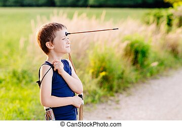 Boy playing playing with bow and toy arrow - Little boy...