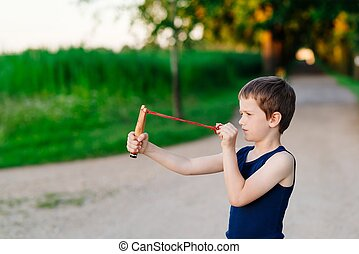 Little boy playing with slingshot at summer afternoon...
