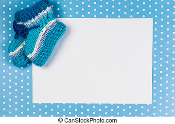 knitted baby socks and blank note on blue polka dot...