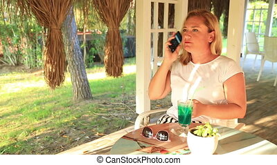 Woman sitting at the summer cafe and using her smartphone