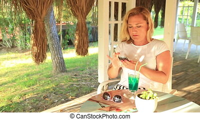 Woman using her smartphone - Blonde middle age woman sitting...