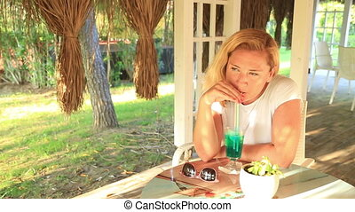 Woman sitting at the summer cafe - Portrait of A Mid Adult...