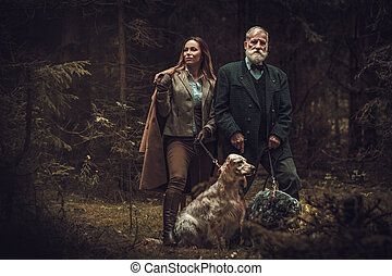 Two hunters with dogs and shotguns in a traditional shooting clothing, posing on a dark forest background.