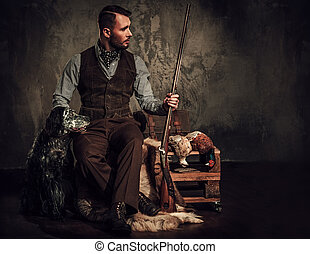 Handsome hunter with a english setter and shotgun in a traditional shooting clothing, sitting on a dark background.