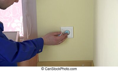Man hand remove safety plug from outlet and insert plug wire...